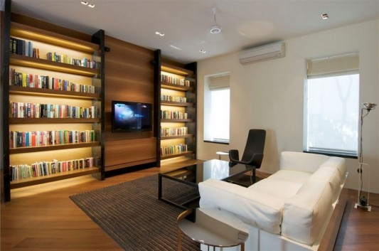 Contemporary home remodel living room with large library bookshelves